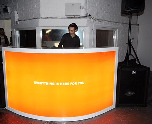 Man behind a DJ booth with the words 'Everything is here for you' written on it.