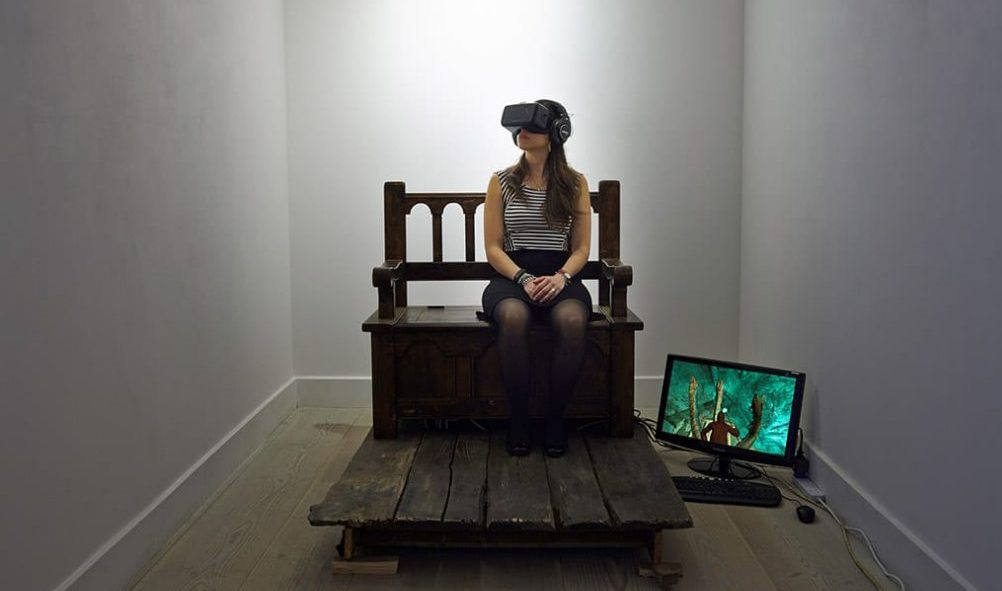 Image of a woman with a headset in a gallery space